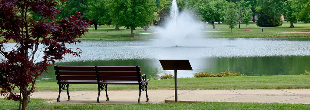 A park bench in front of Legacy Lake