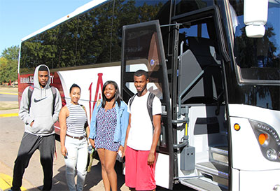 AAMU BTS bus with open doors. Four smiling students pose in front of the bus doors.
