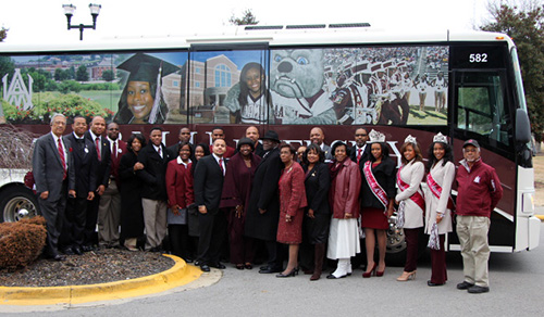 President and staff infront of AAMU bus