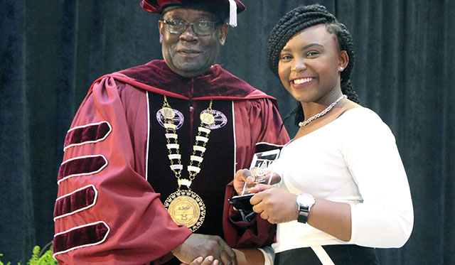 A honors student receives an award from the President of AAMU during the Honors Convocation