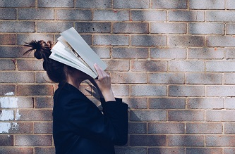 Girl with book over face