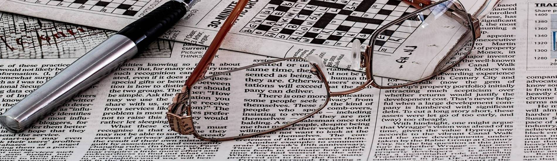 Image of newspaper, crossword puzzle, eyeglasses, and a pen