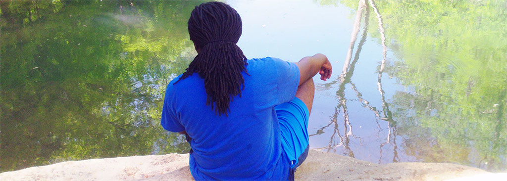 A student sits at the water's edge