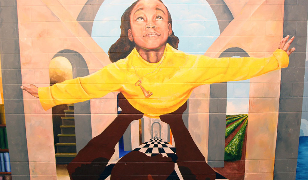 Mural depicting a child being lifted up to the sky
