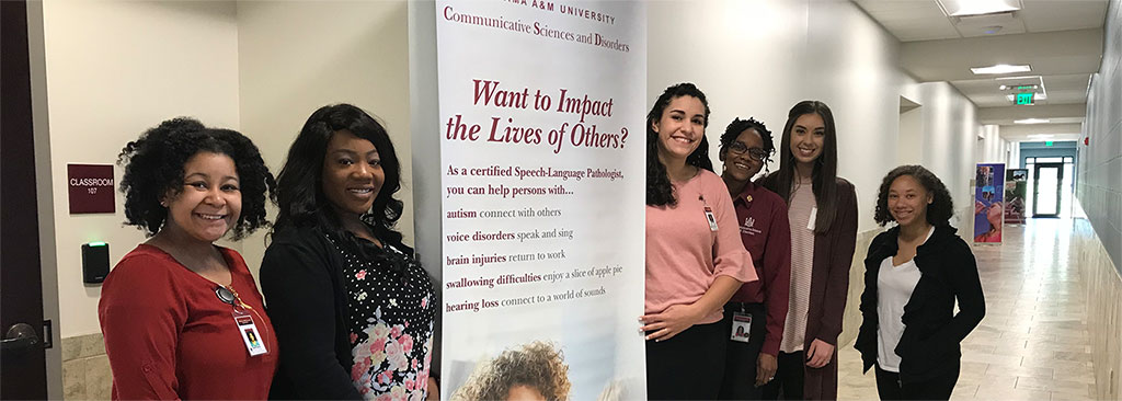 Smiling students pose next to a promotional poster for the Communicative Sciences and Disorders program