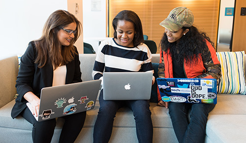 3 female students looking at laptop computers
