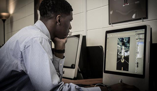 A graphic design student works with image-editing software