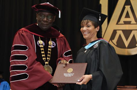 A smiling student receives her diploma from AAMU President Dr. Andrew Hugine