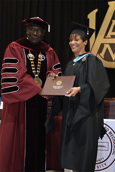 An AAMU graduate receives her diploma at Commencement