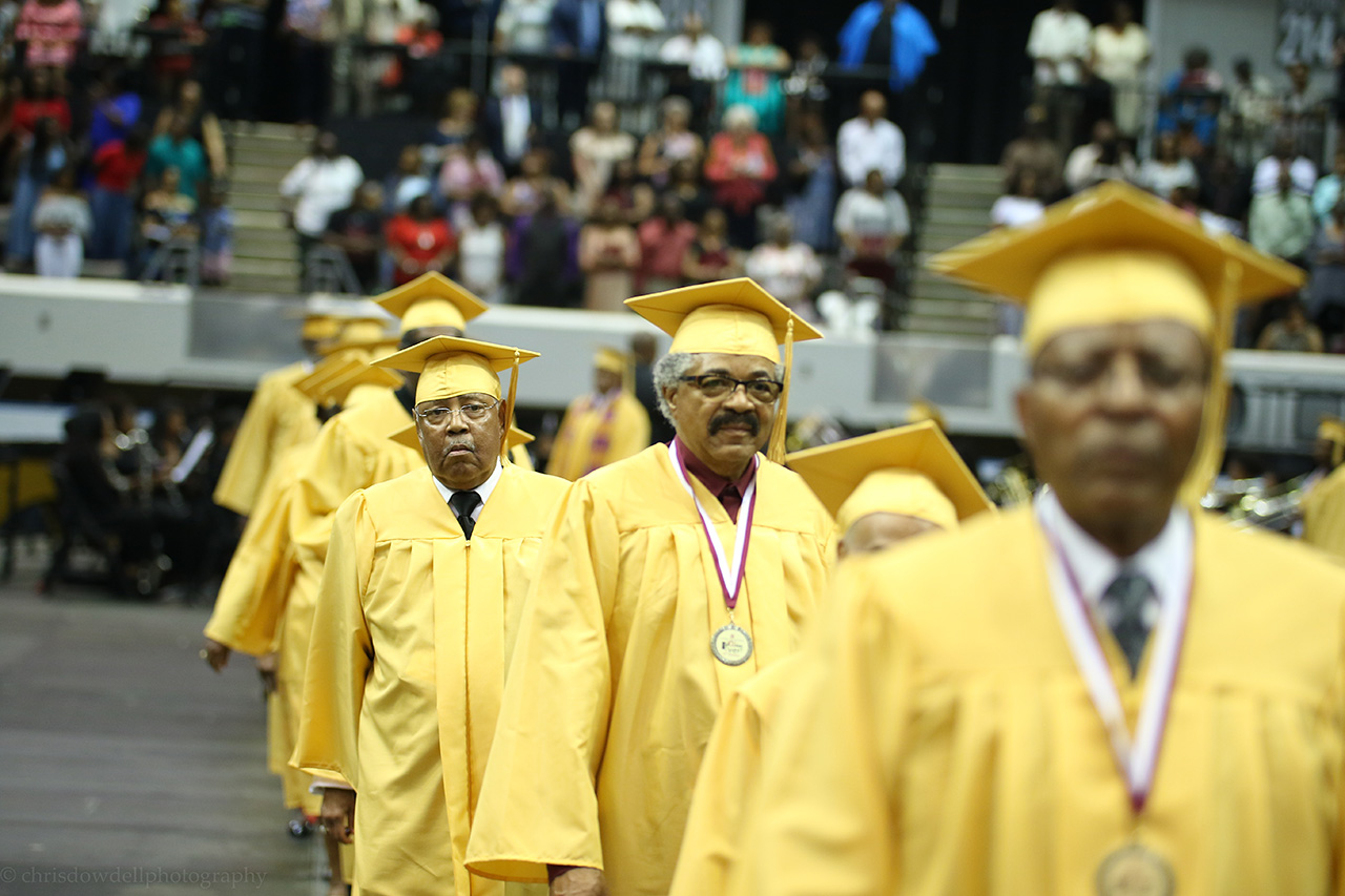 A photo of the golden class walking into commencement.