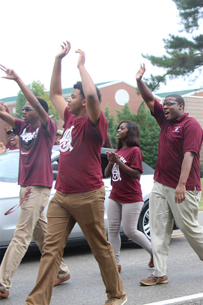 Members of a student organization march and wave in a Homecoming parade