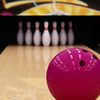 A pink bowling ball moves toward some bowling pins