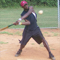 An intramural baseball player swings at a pitch