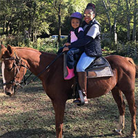 Mother and daughter ride a horse together