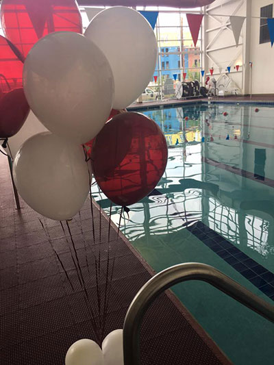 Photo of the Wellness Center's swimming pool with maroon and white balloons in the foreground
